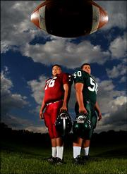 Lawrence High School'S Aaron Kie, left, and Free State High's Phillip Weinmaster pose for the cover of the Journal-World's annual football special section. A variation of the photograph will run Sept. 2 in the Journal-World.