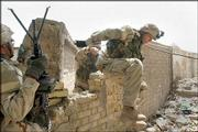 U.S. Army soldiers jump through a cemetery wall during a battle Saturday with insurgents in Najaf, Iraq.