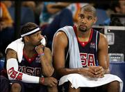 Allen Iverson, left, and Tim Duncan of the United States sit on the bench during a men's basketball preliminary-round game against Lithuania. The Americans lost, 94-90, Saturday at Hellinikon Indoor Arena in Athens, Greece.
