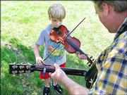 "Matthew Oliphant, 8, warms up playing ""Bill Cheatum"" on fiddle as his father, Ron Oliphant, Chanute, backs him up on guitar. Matthew was entering the fiddle competition at the Kansas State Fiddling and Picking Championships held Sunday in South Park."