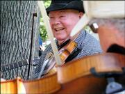 Dave Hendricks, Overland Park, grins as he joins a picking and fiddling jam.
