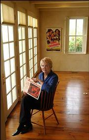 "Cynthia Haines, who teaches film studies at the University of Texas-El Paso, has acquired a particular interest in how Kansas is portrayed in movies. Haines is pictured Friday at her Lawrence home displaying a poster from the classic ""Jayhawkers."""