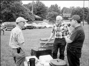 From left, Don Edman, Gary Beasley and Rene Santos, members of the Lawrence Noon Lions Club, grill hot dogs and hamburgers at a picnic for Lawrence residents with visual impairments. The picnic was June 19 at Holcom Park.