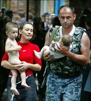 A special forces soldier carries a baby and a woman holds a child after being released by militants in Beslan, North Ossetia. Heavily armed militants released at least 26 women and children Thursday from the provincial Russian school where they were holding more than 350 hostages for the second straight day, officials said.