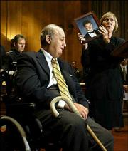 Gun-control advocate James Brady, left, reacts emotionally to a plea by Bryl Phillips-Taylor, of Richmond, Va., as she displays a photo of her son Scott, who was killed by a classmate armed with an AK-47 in 1989. Some congressional Democrats and police leaders from across the country called on President Bush Wednesday to urge Congress to approve the renewal of the assault weapons ban, which is set to expire Monday. Police Chief Joe Polisar, of Garden Grove, Calif., president of the International Association of Chiefs of Police, listens with head bowed at left rear.