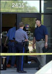 Lawrence police Sgt. Craig Shanks, center, and Detective Lance Flachsbarth, right, talk outside Emprise Bank, 2435 Iowa, shortly after a 2004 bank robbery as another detective enters the