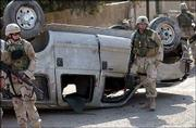 U.S. soldiers inspect a car, reportedly transporting foreigners wearing bulletproof vests and carrying guns, that was attacked by insurgents in Baghdad, Iraq. Eyewitnesses said more than one person was injured in the attack Wednesday.