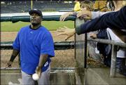 Kansas City's Calvin Pickering hands out signed baseballs during a rain delay. The Royals' scheduled game Wednesday at Detroit was postponed because of rain and will be made up as part of a doubleheader today.