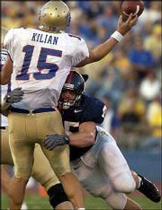 KU's Kevin Kane, right, puts pressure on Tulsa quarterback James Kilian. Kane had a sack and an interception Saturday in his first start.