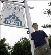 Cape Cod Academy senior M.J. Dean is photographed in front of the school's sign in Osterville, Mass. The T-shirt and cargo pants he wears are now no longer allowed under the school's new dress code.