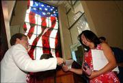 Pamela Williams, left, with U.S. Citizenship and Immigration Services, hands Kate Young-Choi Kim her certificate of citizenship at the Dole Institute of Politics.