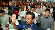 More than 150 people, including Alfredo Martinez, foreground, Kansas City, Kan., are sworn in as U.S. citizens. Forty-nine countries were represented at Friday's ceremony.