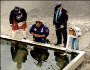 Members of New York City essential services are the first to place flowers in the reflecting pool at the base of the former twin towers of the World Trade Center on the third anniversary of the attacks on the World Trade Center in New York.