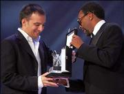 "Spanish movie director Alejandro Amenabar, left, receives the Silver Lion trophy from jury member Spike Lee. Amenabar won the honor Saturday for his movie ""Mar Adentro"" or ""The Sea Within."""