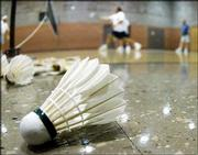 A shuttlecock lies next to the court as six competitors play a game of badminton at the First Presbyterian Church in Hutchinson.