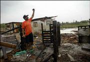 Ernesto Carmenate shows the level that water reached during Hurricane Charley at the remains of his house in El Cajio, about 37 miles south of Havana, Cuba. After Hurricane Ivan passed Cuba on Monday, residents of El Cajio expected a return of severe flooding.