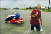 "After gathering as much as he could from his Dauphin Island, Ala., home, Jeff Deen, 52, wades through the island&squot;s already-flooded streets on his way to Mobile, Ala. ""If it&squot;s this bad already, I hate to see what is going to happen later,"" Deen said Wednesday afternoon. ""I may be the last one here. The police are even gone."""