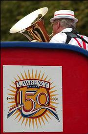 A float carrying a brass ensemble displays the Lawrence sesquicentennial logo.