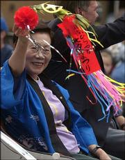 Ritsuko Okura, mayor of Hiratsuka, Japan, one of Lawrence's sister cities, waves to the crowd during the Sesquicentennial Parade on Saturday.