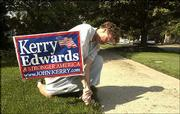 Ellie LeCompte, who lives at 1023 Ky., puts up a Kerry/Edwards sign in her front yard. Lawrence Police have taken numerous reports of signs being vandalized or stolen this election year.