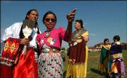 Native dancers, from left, Alayna Ahhaitty, Emma Spottedhorse, 10, Cynthia Sowter, Angie Sandcrane, 7, and Erin Casoose, 7, chat during the opening of the Haskell Indian Nations University 120th birthday powwow. Haskell celebrated its birthday with song and dance Sept. 18 at the university.
