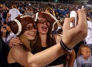 Free State High School seniors Sarah Leslie, left, and Teresa Wilson snap a photo using a camera phone. They attended the FSHS Homecoming football game Sept. 17 against Shawnee Mission Northwest High School at Kansas University's Memorial Stadium.