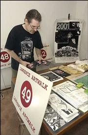 John Wysocki, a Lawrence photographer and organizer of the Lawrence ArtWalk, sorts through posters and guide books from previous years of the annual event. Wysocki and other area artists are gearing up for the 10th anniversary of the self-guided tour of artists' studios.