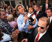 Democratic Presidential candidate Sen. John Kerry, D-Mass., points up at a boom microphone while holding a baby as he works a sidewalk crowd after speaking at a campaign rally Friday at the University of Pennsylvania. Neither Kerry nor Bush campaigned Saturday.
