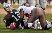 Oakland quarterback Rich Gannon grimaces after being tackled by Tampa Bay linebacker Derrick Brooks. Gannon left the game after breaking a bone in his neck on the play Sunday in Oakland, Calif., and will be sidelined eight weeks.