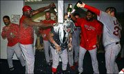 Boston Red Sox players, from left, Dave Roberts, David Ortiz, Tim Wakefield, Ricky Gutierrez and Curtis Leskanic douse Manny Ramirez, center, in the locker room after the team clinched a playoff berth. The Red Sox won, 7-3, Monday night against Tampa Bay in St. Petersburg, Fla.