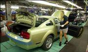 A worker on an assembly line inspects a 2005 Ford Mustang. The car was inspected Monday at the AutoAlliance International plant in Flat Rock, Mich. A 2005 Ford Mustang, pictured below, awaits shipment from the plant.