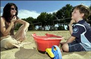 J.R. Blosser, 4, and his mother, Lisa Ann Blosser laugh after he dipped his chin in the sand, giving himself a sandy beard. The pair enjoyed the warm weather while playing Monday in the sand volleyball court near Holcom Park Recreation Center, 2700 W. 27th St.
