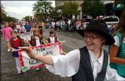 Hannah Whiple, 11, waves to bystanders as she and her Girl Scout troop parade down Massachusetts Street. They participated Sept. 18 in the Sesquicentennial Parade.