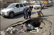 Children look at a crater in Baghdad, Iraq, that was caused by one of the several car bombs that exploded at al-Amel neighborhood. A string of bombs killed 35 children and wounded scores of others as U.S. troops handed out candy Thursday. On Friday, U.S. troops took control of Samarra and claimed they killed more than 100 insurgents and captured 37 in the fighting.