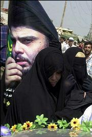A woman holds a poster of rebel Shiite cleric Muqtada al-Sadr as she goes to attend afternoon prayers in Sadr City, in Baghdad, Iraq. Scores of militants, including supporters of al-Sadr, were killed Friday in U.S. airstrikes in the slums of Sadr City, the U.S. military reported.