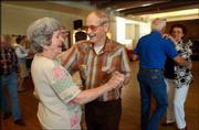 Dottie Miller, left, pair up with Elwyn Welch for a dance at the Douglas County Senior Center, 745 Vt. Jayhawk Area Agency on Aging, which channels state and federal funds to the center, is the subject of a controversy involving a former board member's criticism of the executive director. Miller and Welch danced Wednesday at the center.