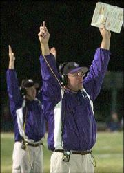 Baldwin High coach Mike Berg signals for a touchdown after a fumble recovery in the end zone against Ottawa. Baldwin won Friday's game, 27-7, at Liston Stadium in Baldwin.