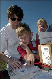 From left, Michele Schneck, Lawrence, and her son Eli, 7, and daughter Karey, 8, fill out postcards to include in the Sesquicentennial Time Capsule. The capsule was buried Sept. 19 at Sesquicentennial Point near Clinton Lake Dam during the closing ceremony of Lawrence's birthday celebration.