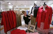 Store manager Stacey Kinyon adjusts clothing at a Janeville store in Bellevue, Wash. She was working Sept. 22 at the store. The nation's apparel merchants are launching new stores to cater to shoppers who are 35 years old and older.