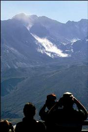 Visitors watch as a large rock slide takes place in the main crater of Mount St. Helens near the Johnson Ridge Observatory in Washington state. Within an hour, the observatory was evacuated Saturday as scientists feared a magma-producing eruption was imminent.