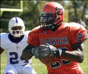 Baker University running back John Reeves (23) tries to elude an Avila defender during the first half. The Wildcats won, 28-7, Saturday at Liston Stadium in Baldwin.
