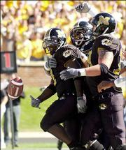 Missouri running back Damien Nash, left, tosses the ball to the referee as he is congratulated by teammates after scoring a touchdown. The Tigers held off the Buffaloes, 17-9, Saturday in Columbia, Mo.