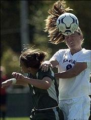 Kansas University sophomore defender Holly Gault, right, heads the ball over Baylor midfielder Lori Viggiano. KU beat the Bears, 3-0, Sunday at Jayhawk Soccer Complex.