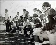 Verner Newman, at center in the police uniform, watches a KU football game from the sidelines in the late 1960s.
