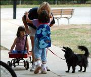 Erin Clyne, center, kisses her mother, Tammy Clyne, goodbye outside Sunset Hills School. Her sister Abby and her dog Star also walked with Erin to school.