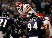 Kansas City running back Priest Holmes (31) dives over Baltimore's Marques Douglas (94), Edgerton Hartwell (56), and Chris McAlister on his way to scoring the game-winning touchdown. The Chiefs picked up their first win this season, a 27-24 victory Monday in Baltimore.