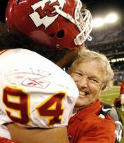 Chiefs coach Dick Vermeil, right, gets a hug from defensive tackle Junior Siavii after the Chiefs edged the Ravens.