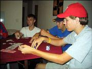 KANSAS UNIVERSITY STUDENT JEREMY KLIEWER, left, Lawrence High School senior Jacob Gage, center, and LHS senior Drew Vogel consider their betting options during a poker game. The players meet every week to play Hold 'Em, a popular poker game.