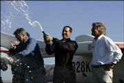 Astronaut Brian Binnie opens a bottle of champaign with Burt Rutan, left, and Richard Branson as they celebrate his suborbital flight to win the $10 million Ansari X Prize. Binnie flew SpaceShipOne Monday from Mojave, Calif.