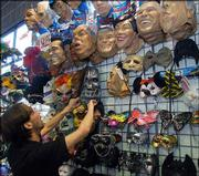 Cosmo Pace, an assistant manager at Costume World in Pittsburgh, lines up a display of masks on the wall. The specialty store offers higher-quality costumes than those found in discount stores.